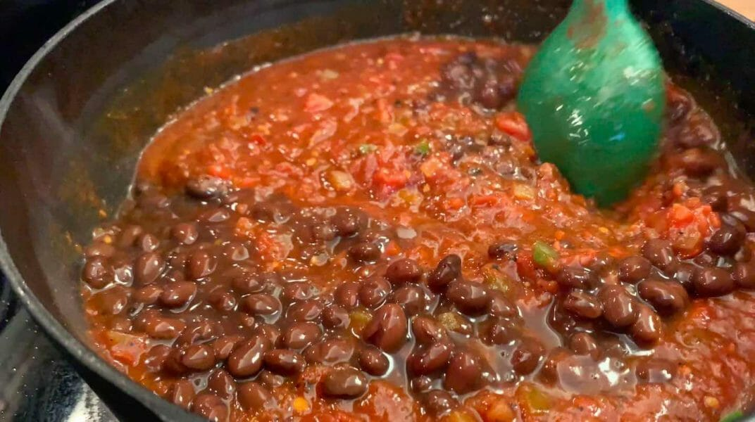 adding canned ingredients to chili