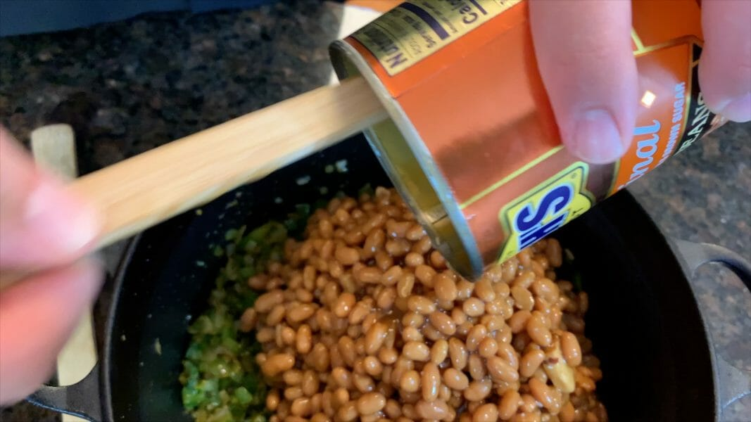 adding baked beans to the pot
