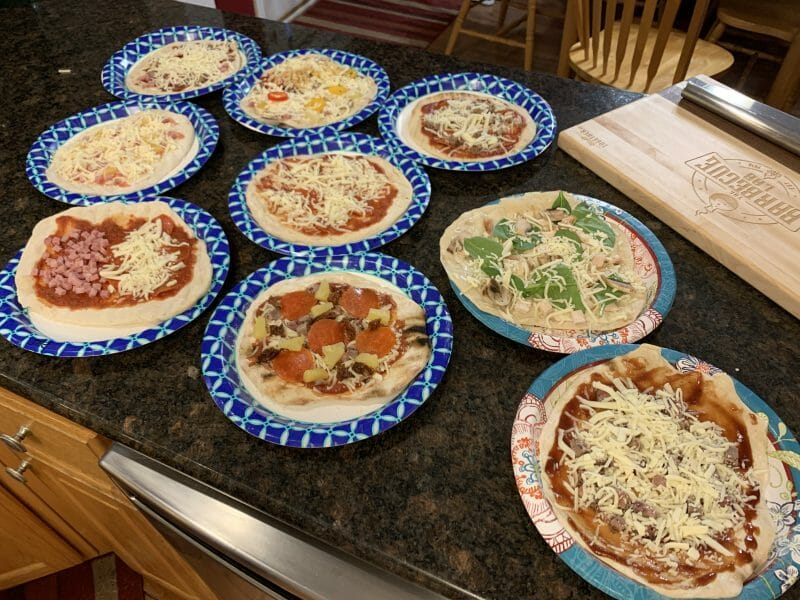 9 different pizzas ready to head to the grill
