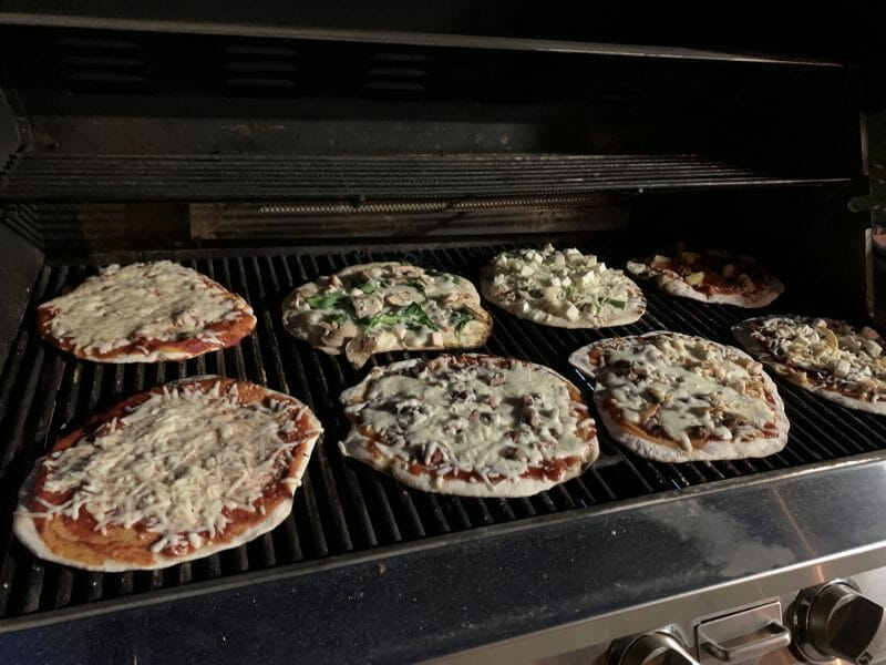 eight pizzas on the grill