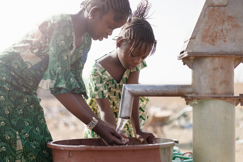 two Ethiopian girls washing their hands in clean water from a well