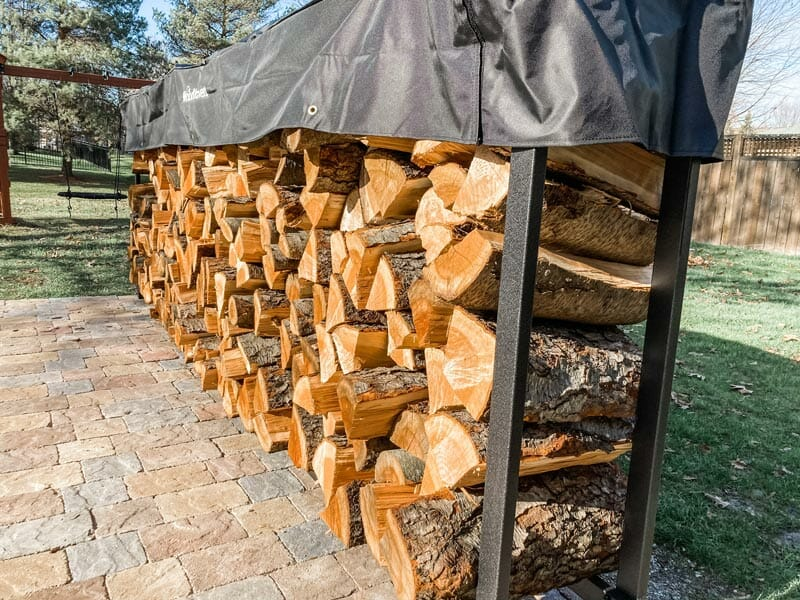 down low view of the 12 foot Woodhaven firewood rack loaded with cherry wood splits