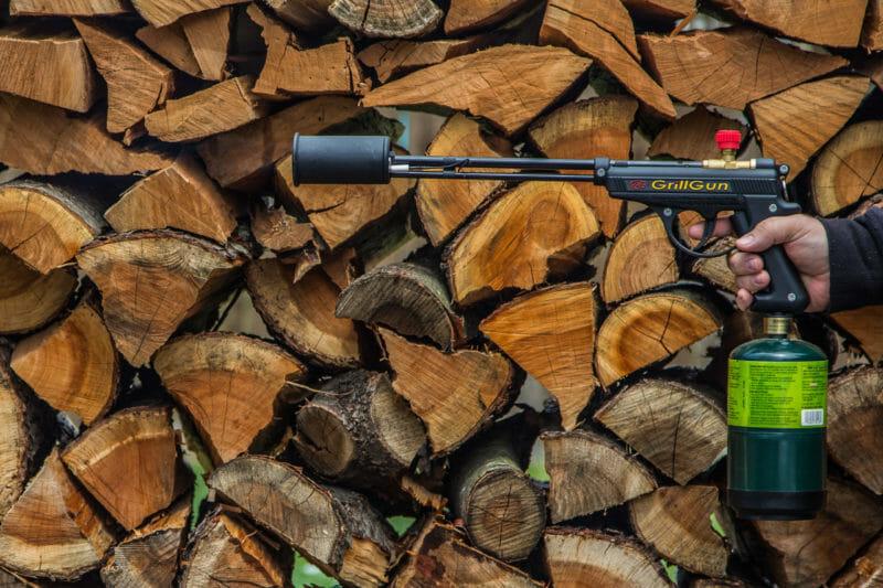 GrillGun in front of a log rack