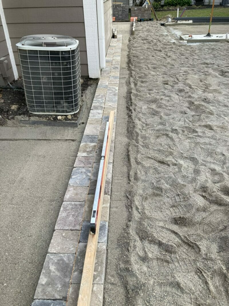 2 rows of pavers sitting on paver sand with a level