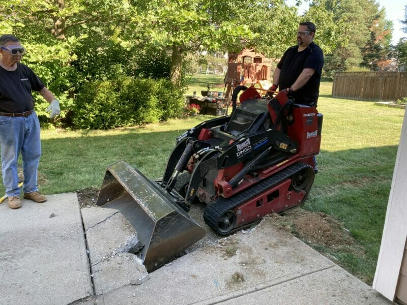 David using the skid steer to demolish old patio