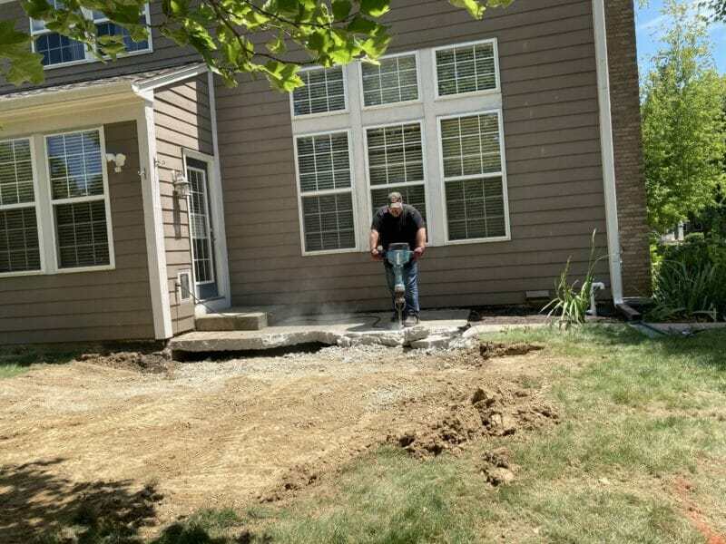 David using a jackhammer to break up the concrete slab