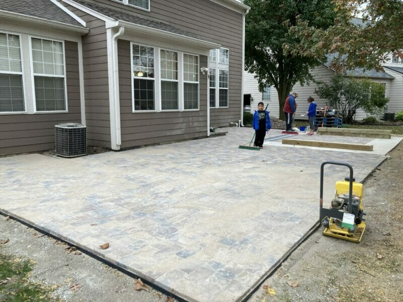 sweeping polymeric sand between the pavers