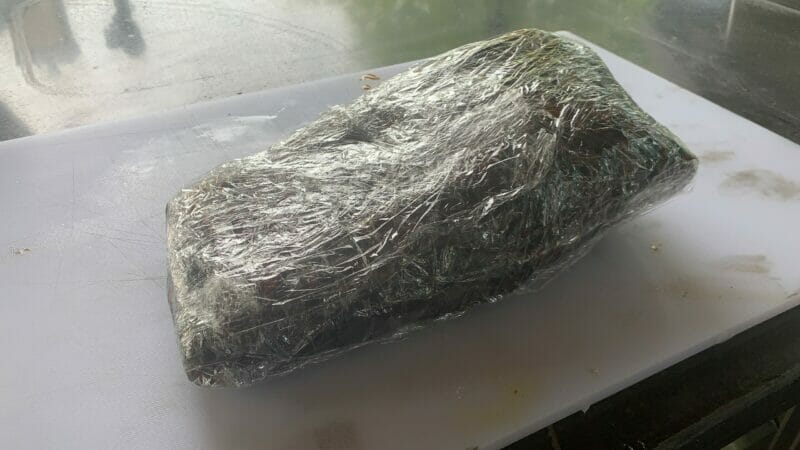 smoked brisket wrapped in butcher paper wrapped in plastic wrap for the rest